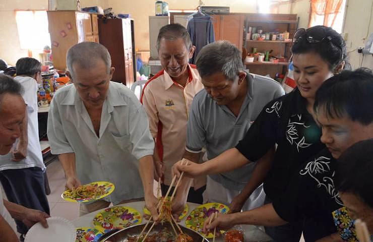 Prosperous toss: Elderly tossed yee sang with village headman, Wong Huey Yam (third from left), Resort's Director of Marketing Communications, Connie Chin (third from right) and Chinese Chef, Wang Huee Suan (second from right) together to ring in good fortune and auspicious year of the Snake.