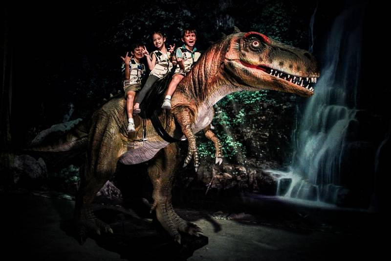 Children experiencing riding the T-rex at Dinoscovery
