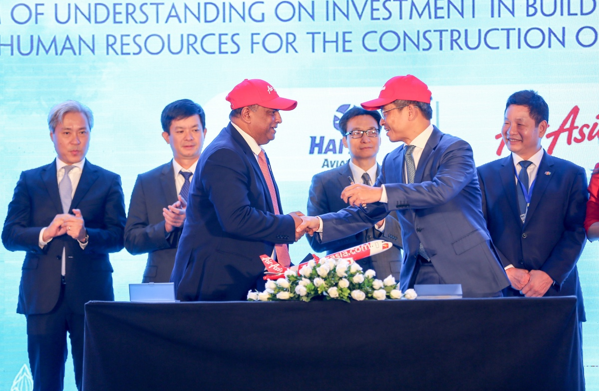AirAsia Group CEO Tony Fernandes (front centre left) shakes hands with Tran Trong Kien, CEO of Thien Minh Travel Joint Stock Company CEO and General Director of Hai Au Aviation Joint Stock Company, after the memorandum signing witnessed by Vietnamese Deputy Prime Minister Vu Duc Dam (centre right) and Vietnamese Deputy Minister of Culture, Sports and Tourism Le Quang Tung (centre left), flanked by the Vice Chairmen of the Vietnamese Advisory Council to the Prime Minister on Administrative Procedures Reform, VinaCapital Group CO-Founder and CEO Don Lam (far left) and FPT Corporation Co-Founder, Chairman and CEO Truong Gia Binh (far right), who is also Chairman of Vietnam's Private Sector Development Committee.