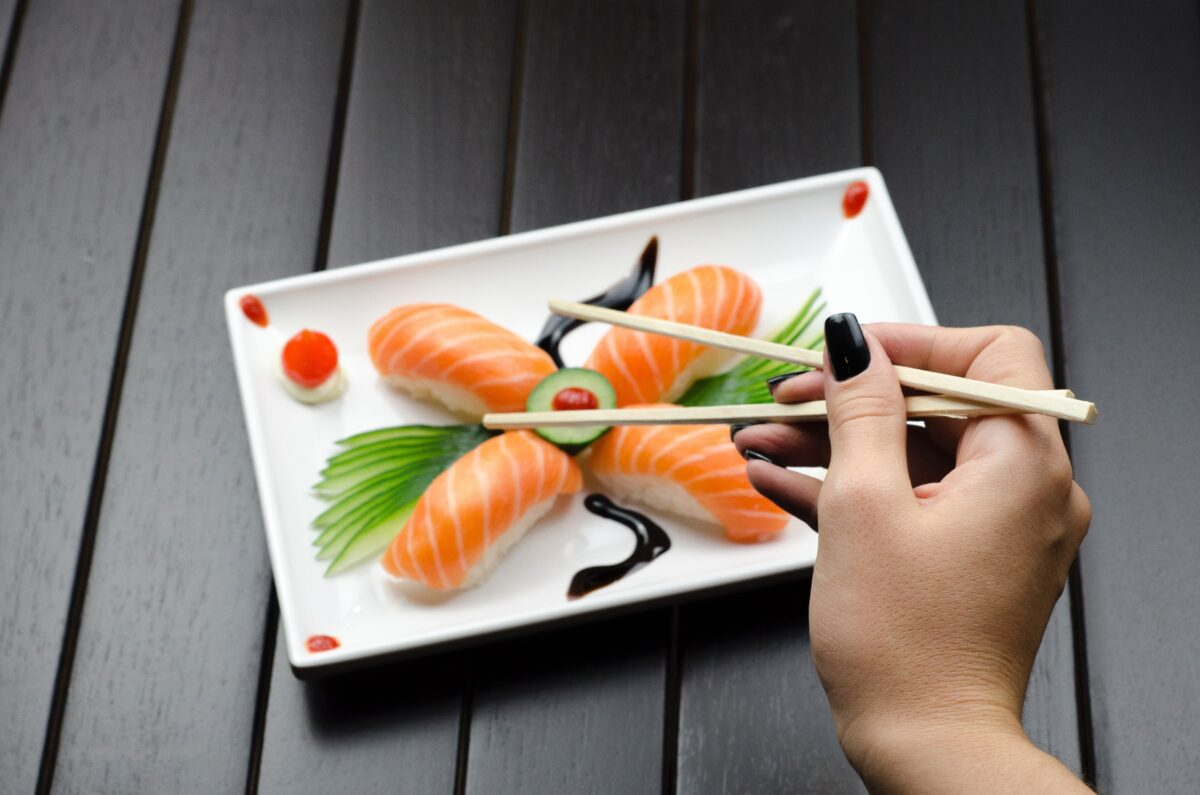 Eating sushi with wooden chopstick